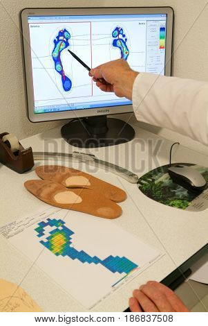 Doctor Preparing Orthopedic Insoles For A Patient