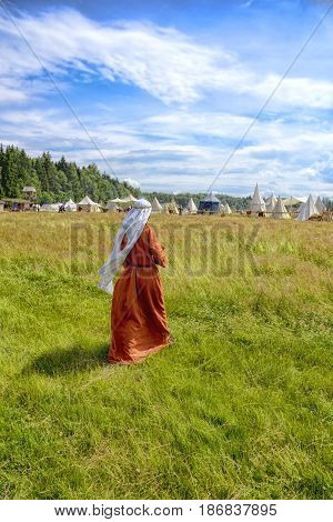 the woman in a medieval dress goes on a grass to Medieval campground
