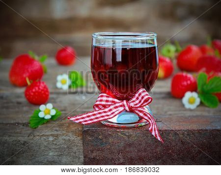 homemade liqueur from strawberries and fresh flowers and berries on a wooden Board