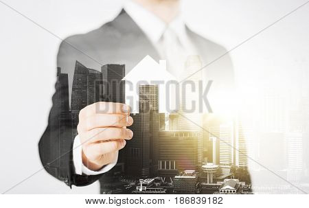 business, people and mortgage concept - close up of businessman holding paper house over city with double exposure