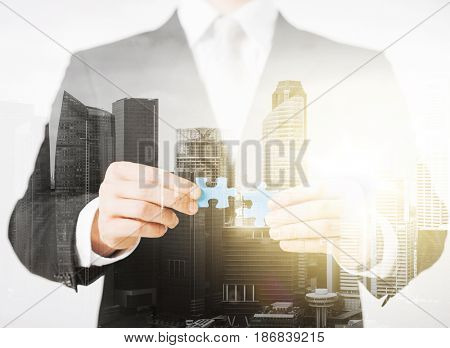people, business and management concept - close up of businessman with puzzle pieces over city with double exposure