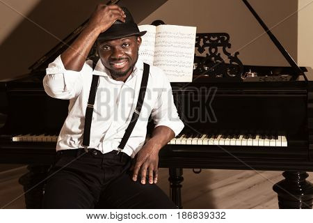 Afro American man in hat with piano