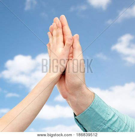 family, childhood, fatherhood and people concept - father and child holding hands together or making high five over blue sky and clouds background