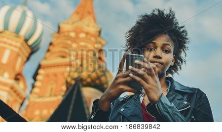 Young beautiful biracial tourist girl with curly afro hair talking with her family via smart phone while standing in front of Saint Basil's Cathedral in Russia Moscow on sunny summer evening