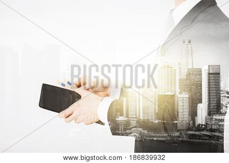 business, finances and people concept - close up of businessman with euro money in wallet over city with double exposure