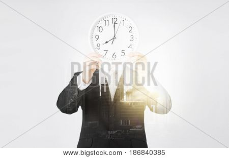 people, business and time concept - businessman covering his face behind wall clock over city with double exposure