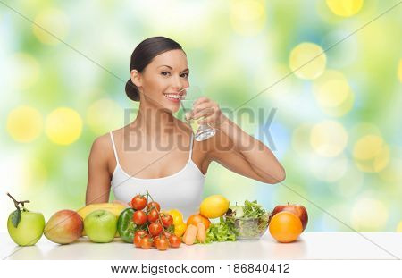 people, diet, healthy eating and food concept - happy woman drinking water from glass with fruits and vegetables on table over green summer lights background