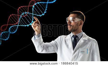 science, genetics and people concept - male doctor or scientist in white coat and safety glasses touching touching virtual projection of dna molecule over black background
