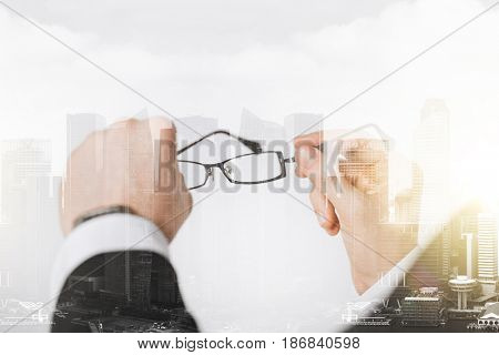 people, business and vision concept - close up of businessman hands holding glasses over city with double exposure