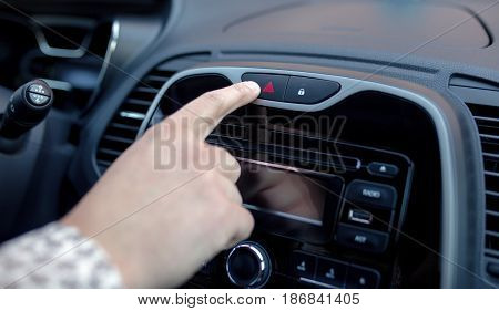 Male hand pressing emergency warning button on car console closeup