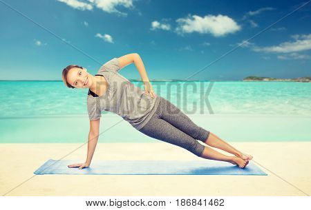 fitness, sport, people and healthy lifestyle concept - woman making yoga in side plank pose on mat over beach background