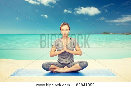 fitness, sport, people and healthy lifestyle concept - woman making yoga meditation in lotus pose on mat over sea and sky background