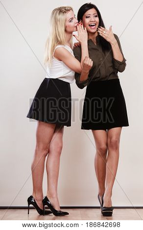 Two women multiethnic whispering and smiling sharing their secrets full length studio shot