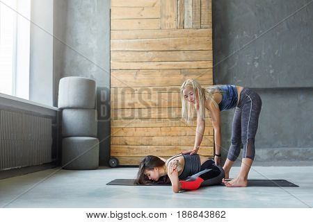 Yoga class teacher and beginner making asana exercises. Instructor assists to make cobbler pose, baddha konasana. Healthy lifestyle in fitness club. Stretching with coach
