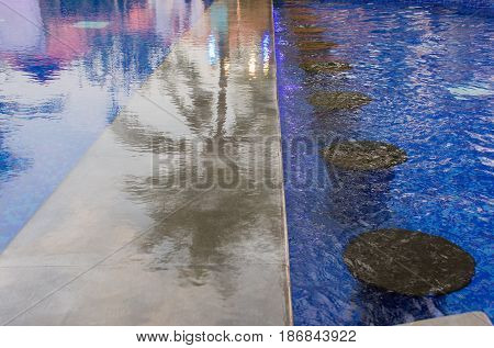 Reflection of palms tree shadow with pool water in the evening light motion of water in the pool