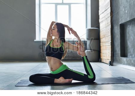 Woman in yoga class making asana mermaid pose. Variation of rajakapotasana. Healthy lifestyle in fitness club. Stretching