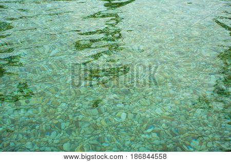 Looking to Movement of Crystal clear water surface through stone in hot spring water