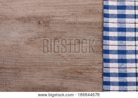 blue checkered tablecloth on an old wooden table with copy space for your text. Top view.