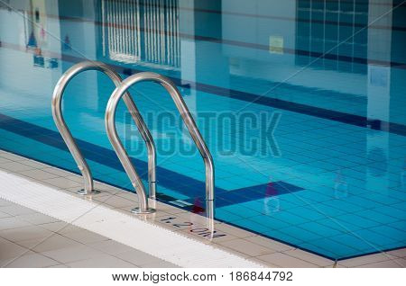 Soft focused picture of stainless steel Stairs down to the poolwith Reflection in the pool
