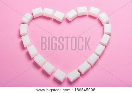 Heart made of cubes of sugar on a pink background. Empty place for text copy paste
