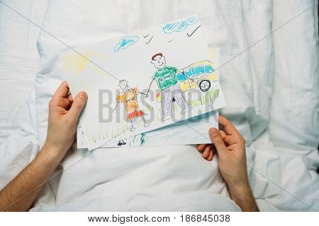 sick father holding drawings while laying on hospital bed at ward hospital patient bed