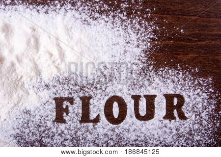 The word flour is written on the table. Flour is scattered on brown discs