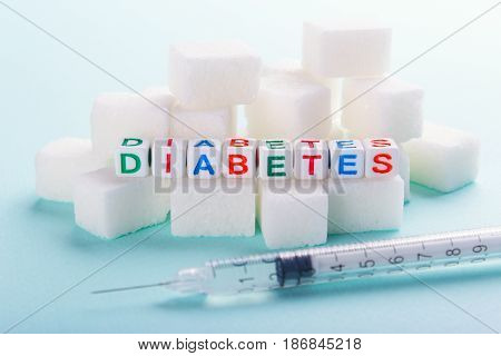 Insulin syringe from diabetes along with sugar cubes.