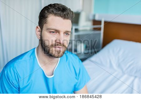 Portrait Of Young Sick Man Sitting On Hospital Bed, Hospital Bed Patient