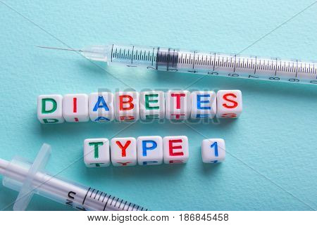 Diabetes of the first type and an insulin syringe on a green background