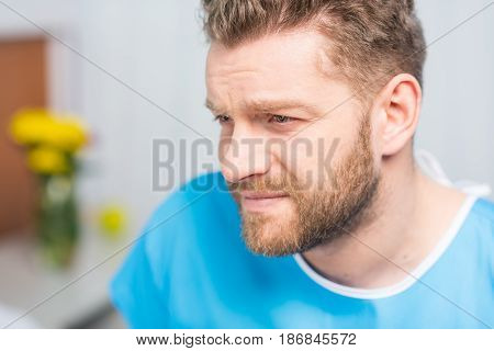 Close-up Portrait Of Sick Bearded Man Looking Away In Hospital