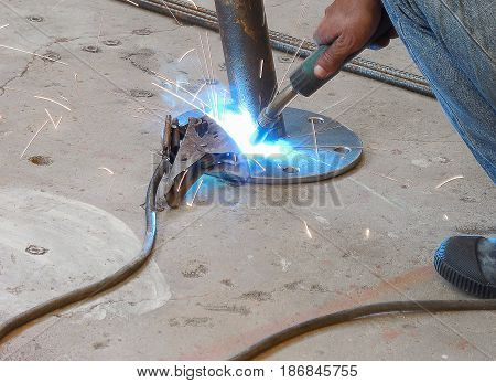 Soft focused picture of Worker man is welding round steel pipe and footplate by welding machine in factory