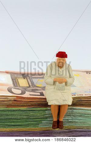 senior sitting on banknotes