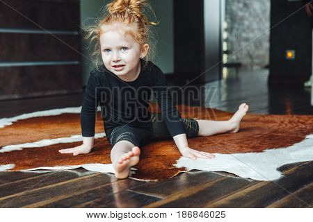 Little girl performs a twine at home on the floor