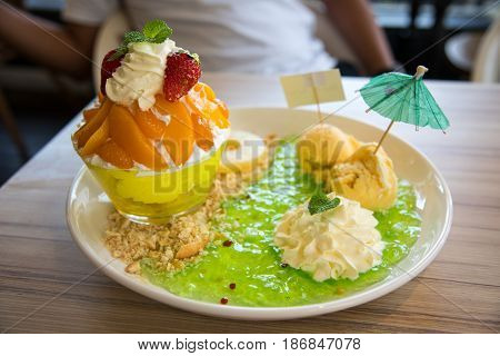 an Gelatin dessert menu ice cream with whip cream and fruit and cookie.