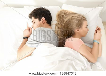 Young couple with sleep trackers resting in bed at home