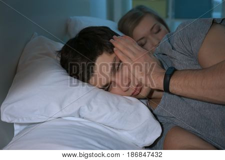 Young man with sleep disorder lying on bed at home