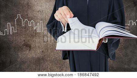 Digital composite of Judge holding book in front of grunge wall with city drawings