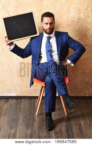 marketing. serious businessman in suit holding a blackboard