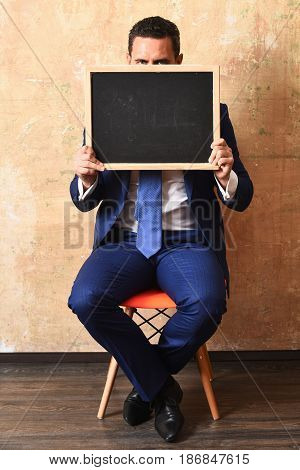 businessman or man hiding holding a blackboard copy space harassment