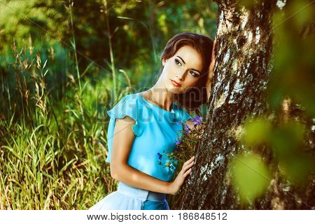 A woman in the woods leaned against a tree