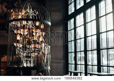 old chandelier with cobwebs against the background of a large window