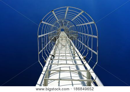 White iron staircase on the pipe rises into the blue sky without clouds