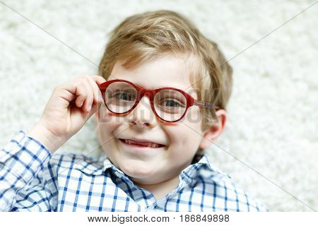 Close-up portrait of little blond kid boy with brown eyeglasses on white background. Happy smiling child in casual clothes. Childhood, vision, eyewear, optician store. Boy choosing new glasses