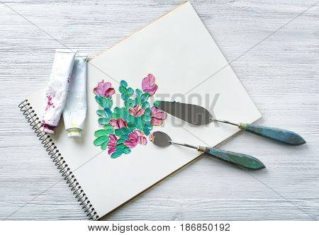 Album with picture made of oil paint strokes and craftsman's tools on white wooden background