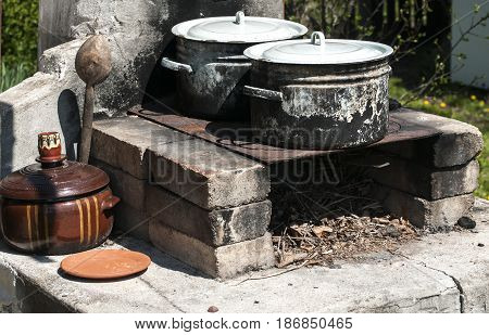 Old burnt soot enameled saucepots on outdoor fireplace in village courtyard