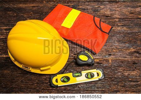 Construction tools or safety equipment with yellow helmet on wooden table.