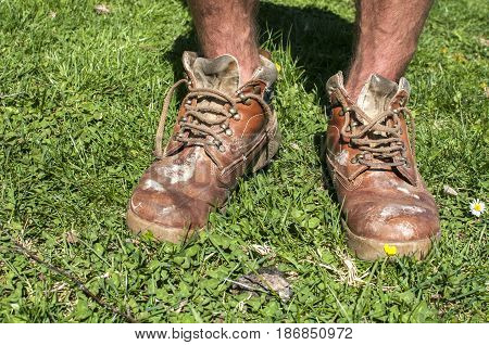 Man legs in old used weathered moldy grunge leather shoes on green grass field