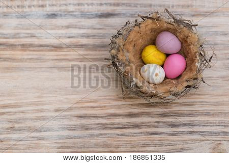 Small bird nest with coloured easter eggs on timber background