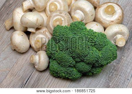 Broccoli and mushrooms on a wooden table. Horizontal photo.