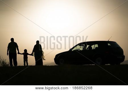 Silhouette of happy muslim family holding each other hands coming with car for picnic in nature